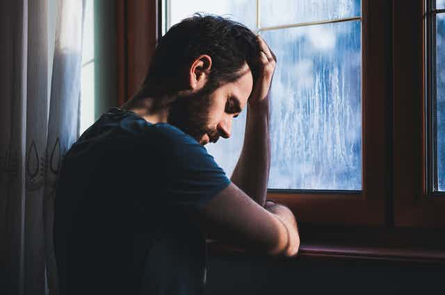 A man leans on a window sill, looking despondent.