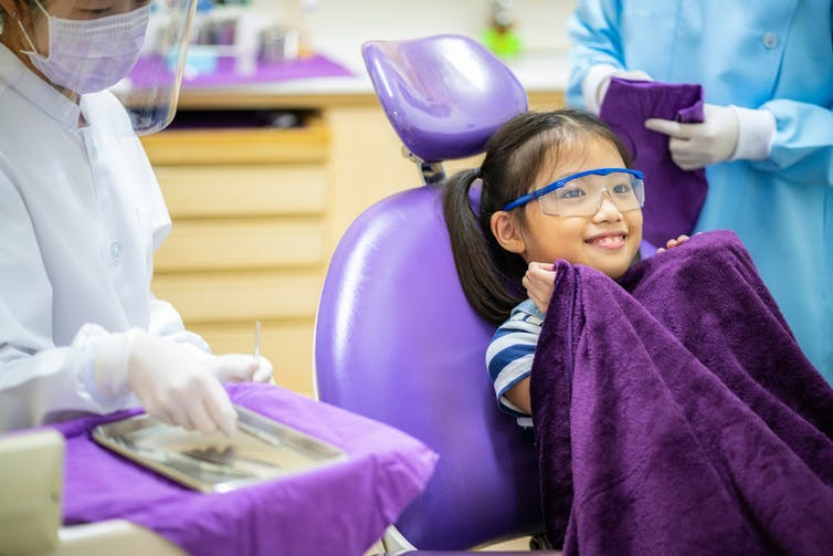 Child sits in a dentist's chair, holding a purple blanket to her chin.