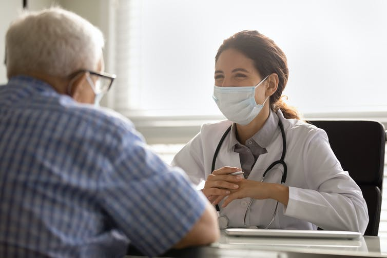 Specialist doctor at a desk talks to a patient, who sits facing her.