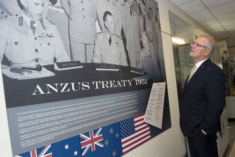 A man in a suit looks at a poster on a wall.