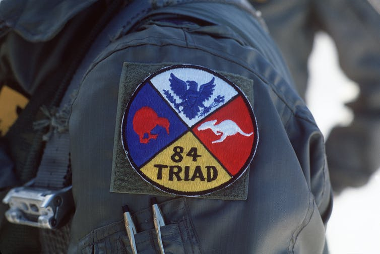 A circular military patch showing an eagle, a kiwi and a kangaroo