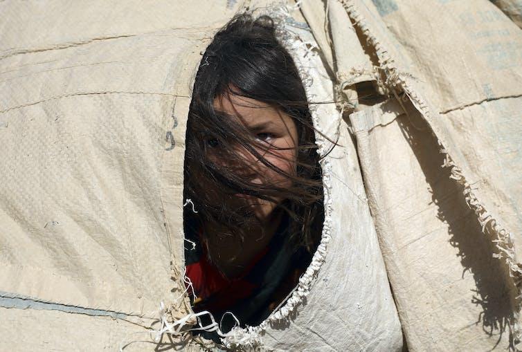 Una niña afgana mira desde la solapa de una tienda de campaña, con el pelo tapándole la cara