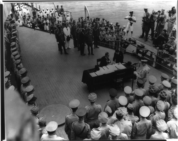 A black and white image of officials signing a document aboard a warship