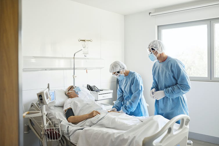 Doctors treating elderly man during COVID-19 pandemic