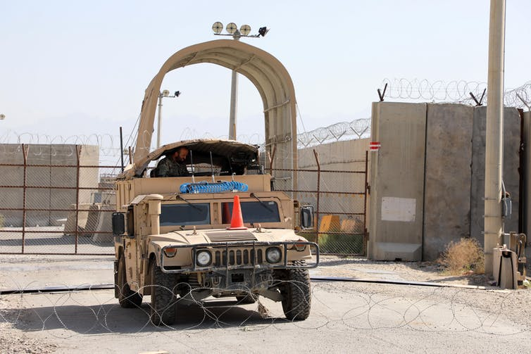 A military vehicle sits between a fence and a roll of barbed wire