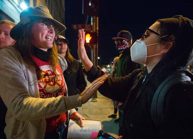 one unmasked woman argues with another who is wearing a mask, both holding up their hands