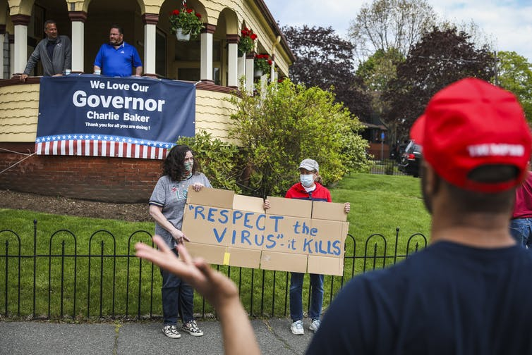 two masked people hold homemade sign that reads 'Respect the virus, it kills'