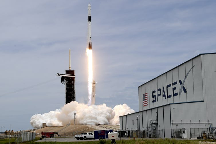A rocket launches in the background, a SpaceX building in the foreground