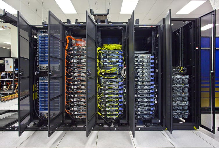 A stack of computer servers with brightly coloured wires
