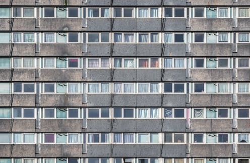 The facade of a council housing tower block in London, showing rows of gray concrete and windows