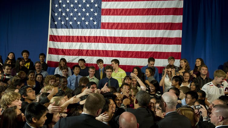 President Barack Obama shakes hands with students with large US flag in backdrop