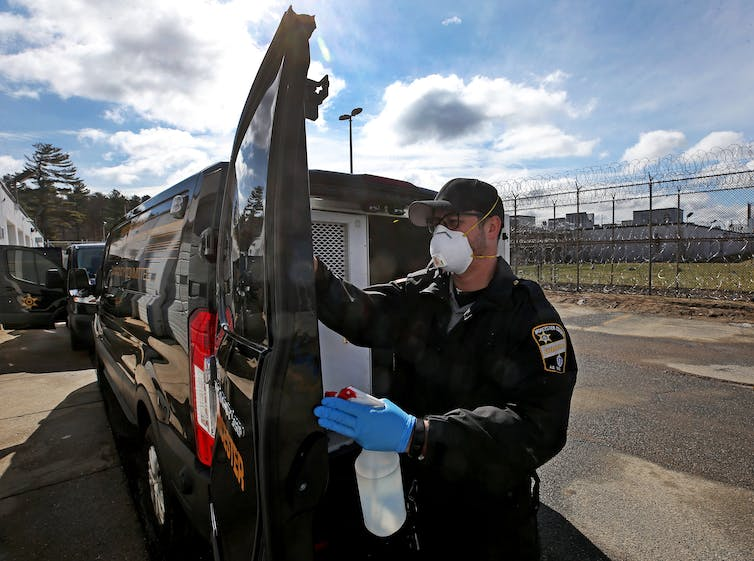Wearing a protective mask and gloves, a correctional officer sanitizes an inmate transport van.