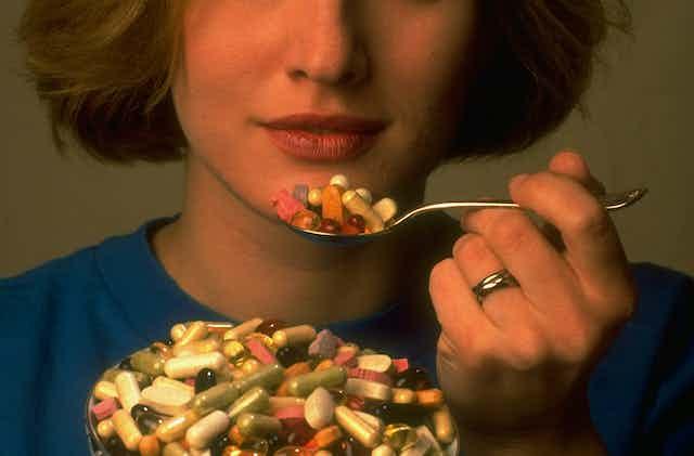 A woman eats a spoonful of pills.