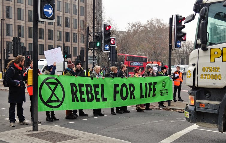 Protestors carry a banner reading 'Rebel For Life'