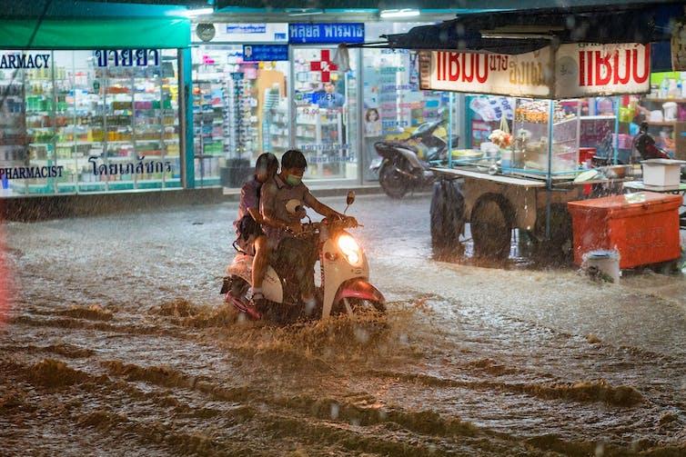 People ride a motorbike through rain and heavy floods amid city lights