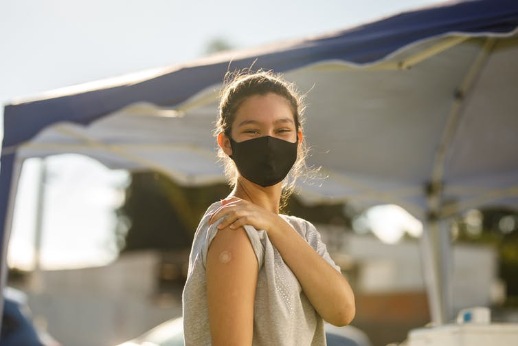 Teen girl wearing a mask and showing a bandaid on her forearm