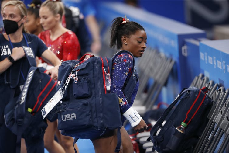Simon Biles carrying bag in Olympic costume