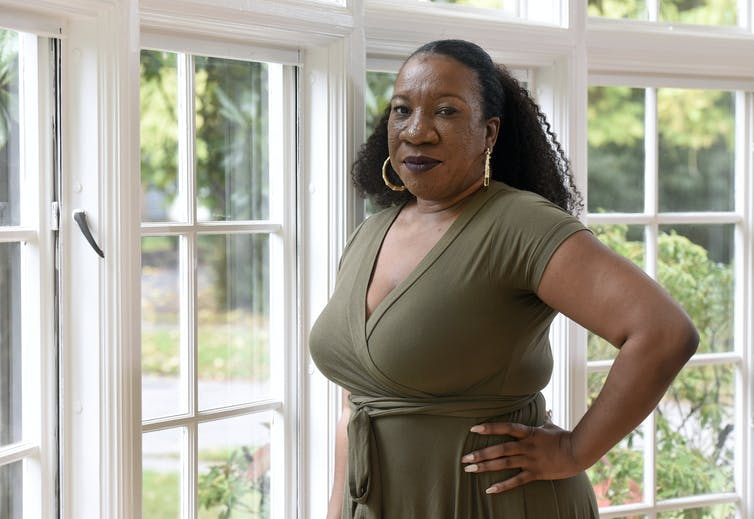 Tarana Burke stands near a window with her hands resting on her hips.