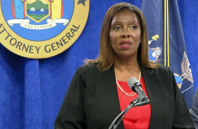 Letitia James stands in front of a microphone with the attorney general seal on a blue curtain behind her during a press conference