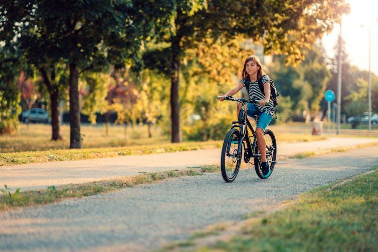 girl rides bike through park