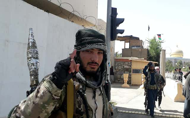 A Taliban militant looks toward the camera and holds up his index finger