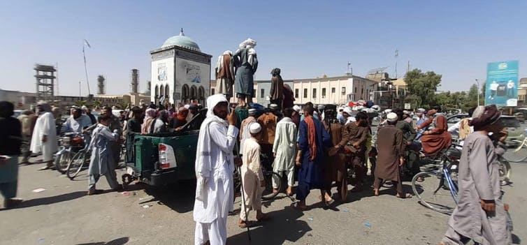 Afghans look on as Taliban militants gather around the main square after taking control of Kandahar