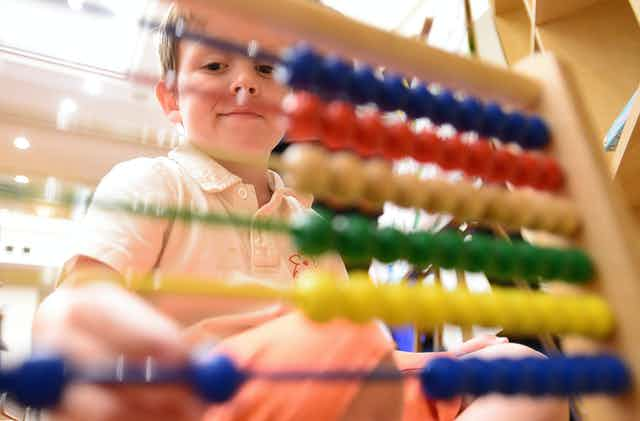 A boy plays with an abacus.
