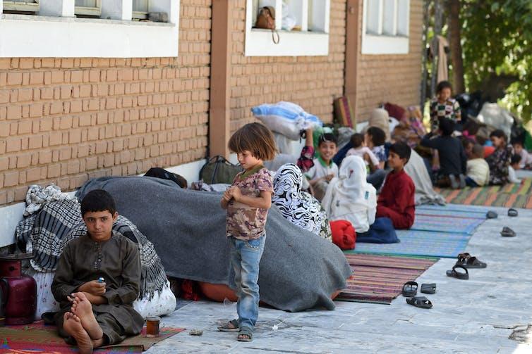 Children sit on carpets outside a brick building