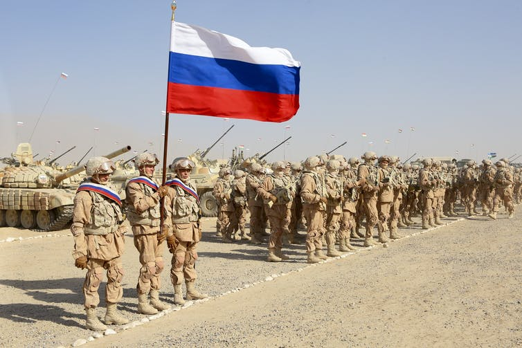 A group of soldiers stands alongside armored vehicles with a Russian flag flying overhead.