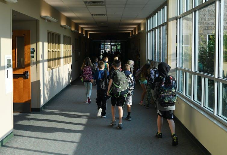 Students wearing backpacks walk down school corridor