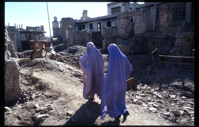 Women in purple burqas walk amid a ruined city street