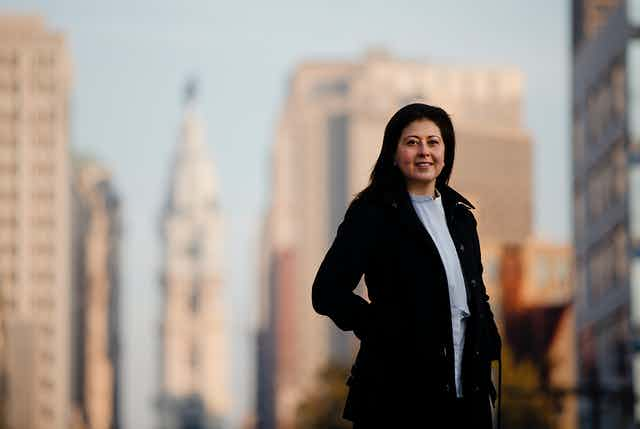 A woman stands for a photo in front of the Philadelphia skyline
