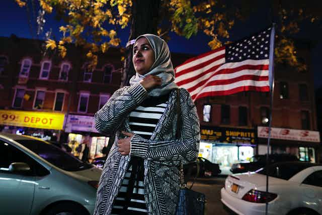 A young woman wearing a headscarf stands on a street in front of an American flag