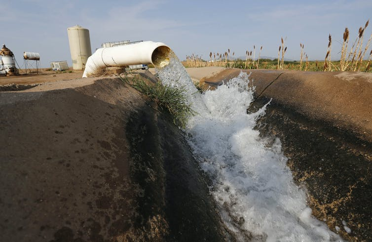Water flows into a canal that feeds farms in Casa Grande, Ariz.