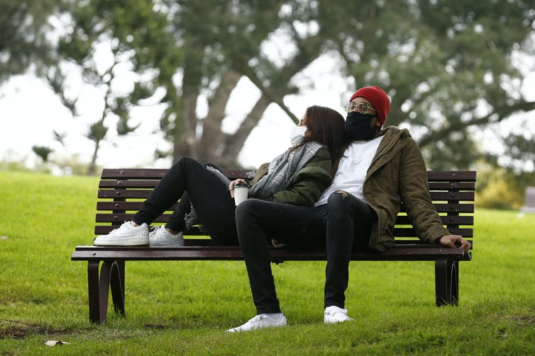 Couple in masks, flopped on a park bench.