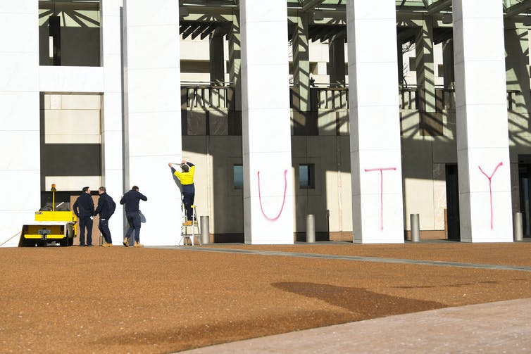 Climate change graffiti is cleaned off the walls of parliament house.