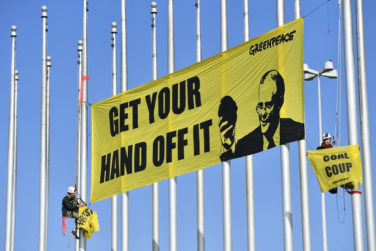 An anti-coal banner is hung by activists at federal parliament in 2018.