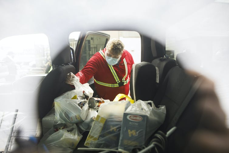 A volunteer wearing a mask collects bags of donated food from the back of a vehicle.