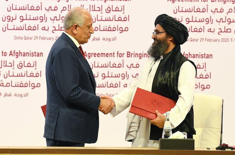 Khalilzad and Taliban co-founder shake hands.