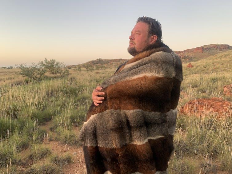Tiriki stands in an open desert, wearing a cloak.