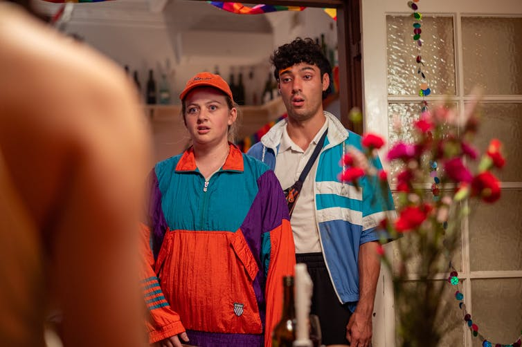 A man and a woman in brightly-coloured windcheaters, staring in silent awe into a party scene