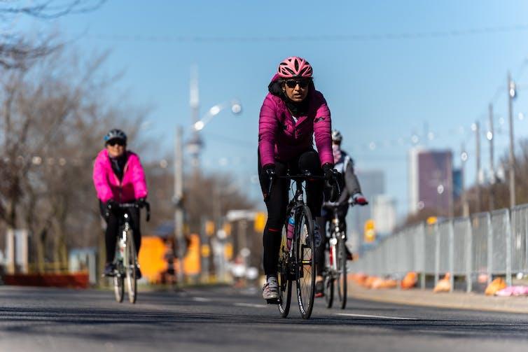 Three cyclists bike along a closed road downtown Toronto