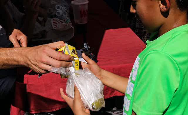 A school boy gets served lunch in a bag.