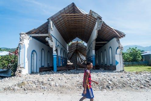 A man walks past a church destroyed during an earthquake in Haiti.