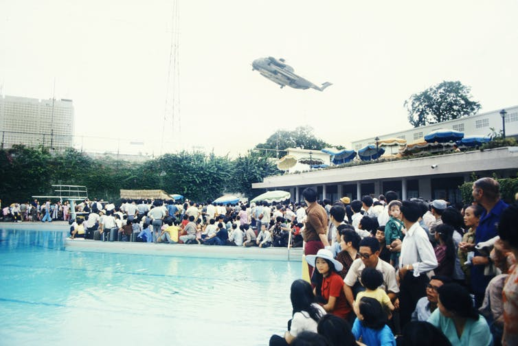 A crowd of people surrounds a swimming pool while a helicopter flies overhead