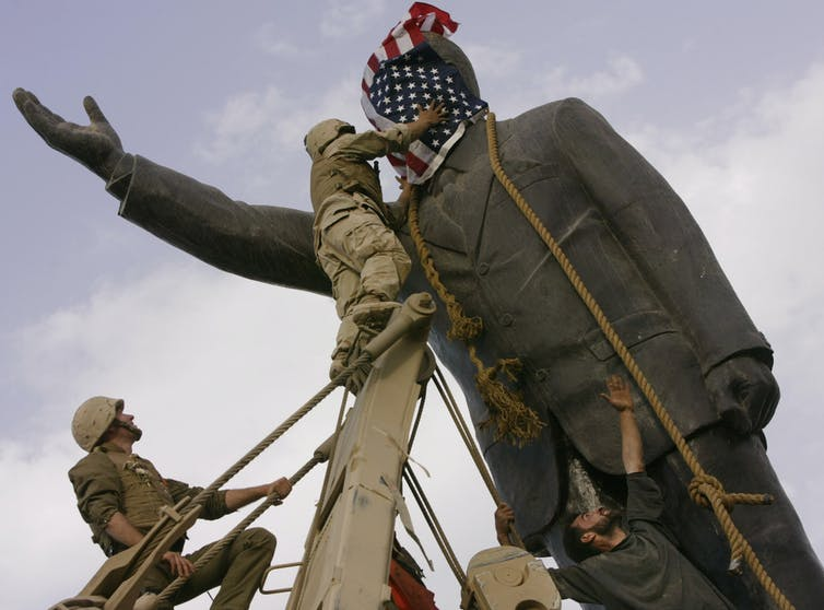 A man on a ladder covers a statue's face with a U.S. flag