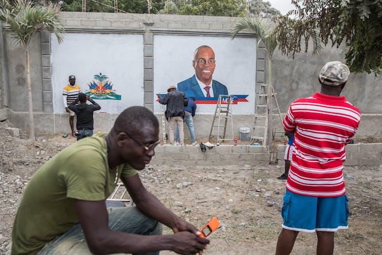 Local artists paint a mural of slain president Jovenel Moise.