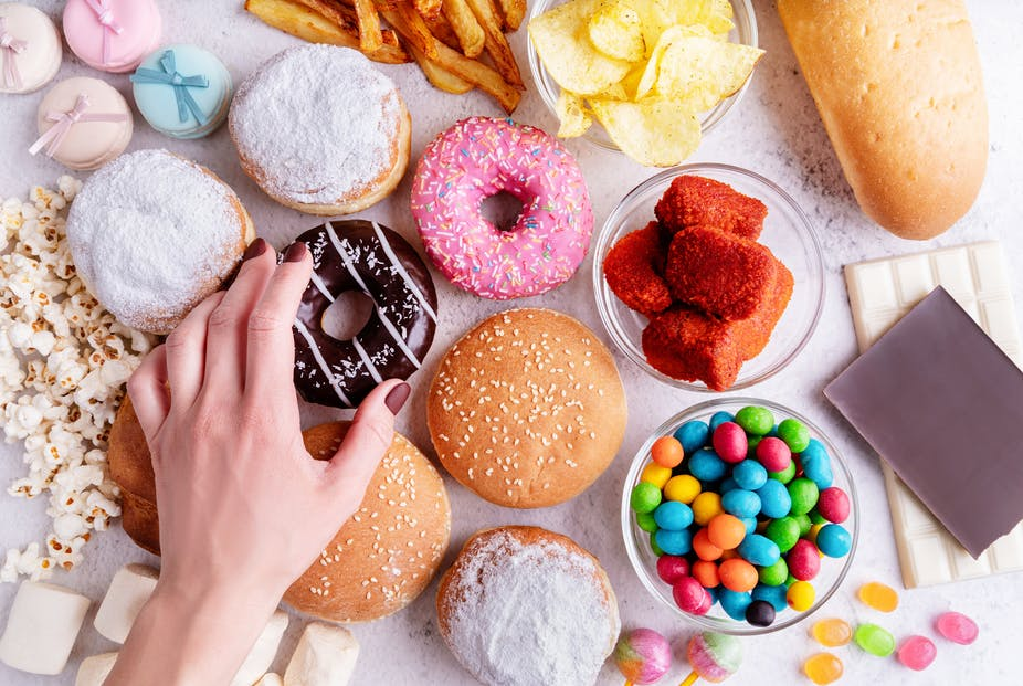 A woman's hand reaches for a donut, which is nestled among other sugary foods on a table, including candies and bread.
