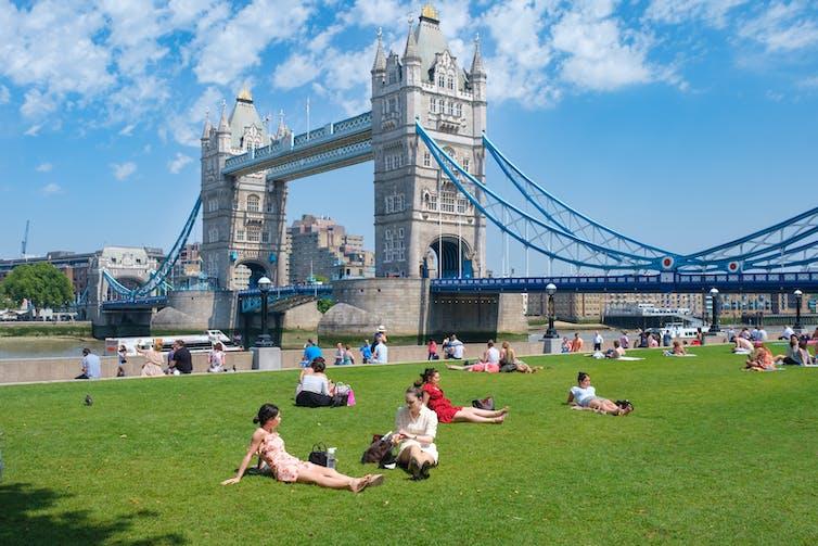 People sit on grass bank near Tower Bridge.