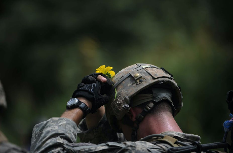 A US soldier in Afghanistan attaches a yellow flower to his helmet.